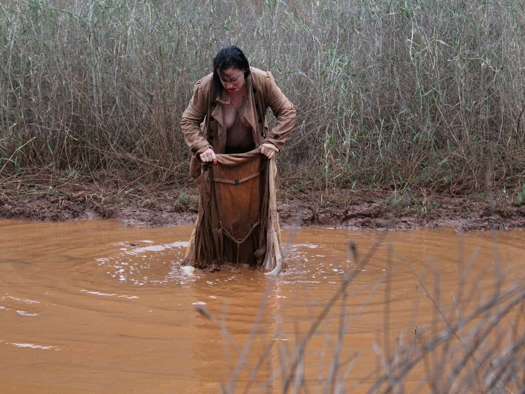A woman with black hair and a brown coat stands in a pool of muddy water. Her coat is slightly open which partially reveals her breasts. She looks angry and has her head tilted down towards her feet. She holds a brown water-soaked coat with her two hands. She looks as if she is washing the coat in the water.